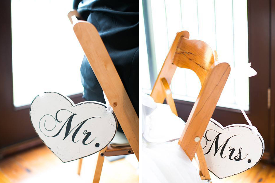 Wooden sweetheart table chairs with Mr. and Mrs. signs hanging on back.