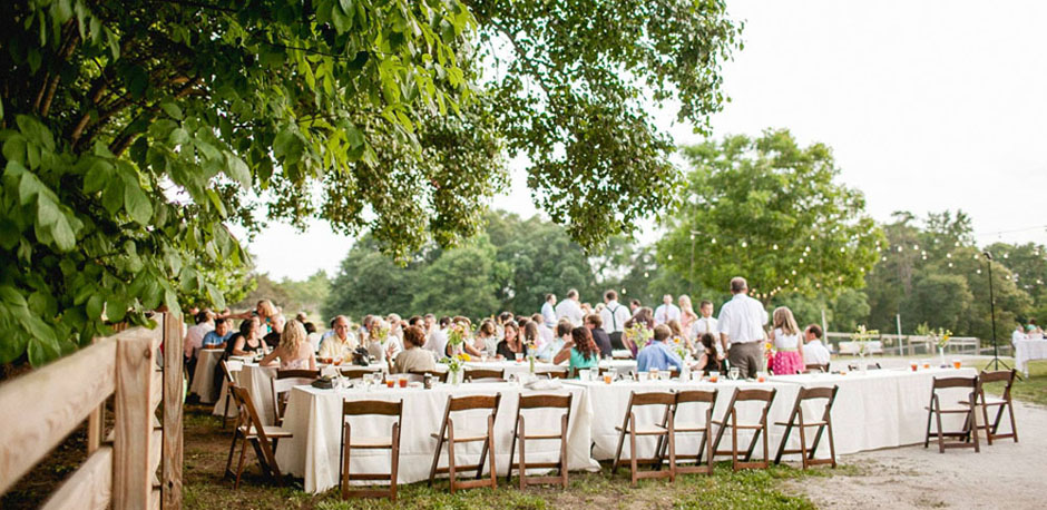 Outdoor Farm Wedding Reception With Long Rectangular Tables And Folding  Chairs.