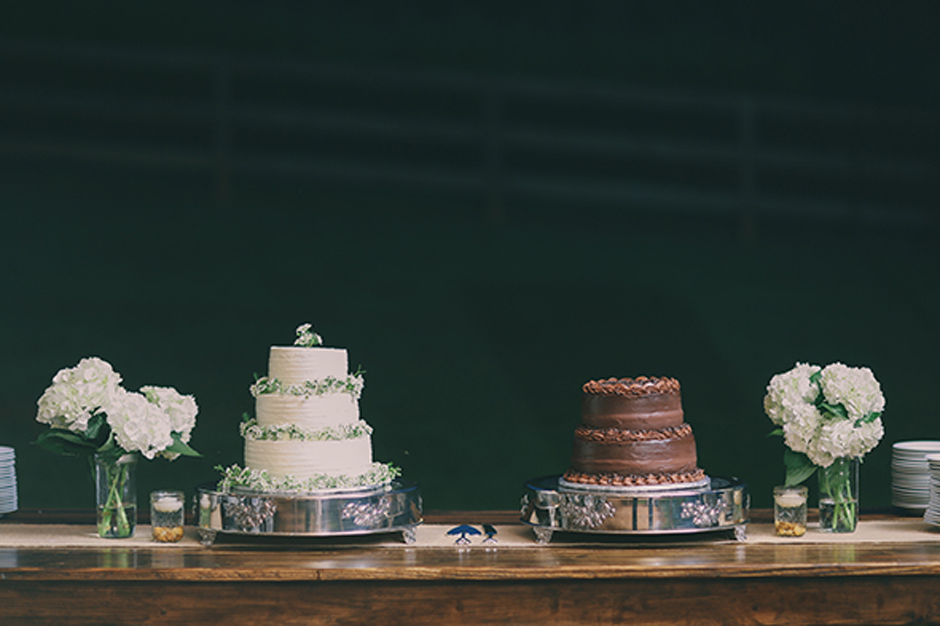 Bride and groom's cakes atop a farm table.