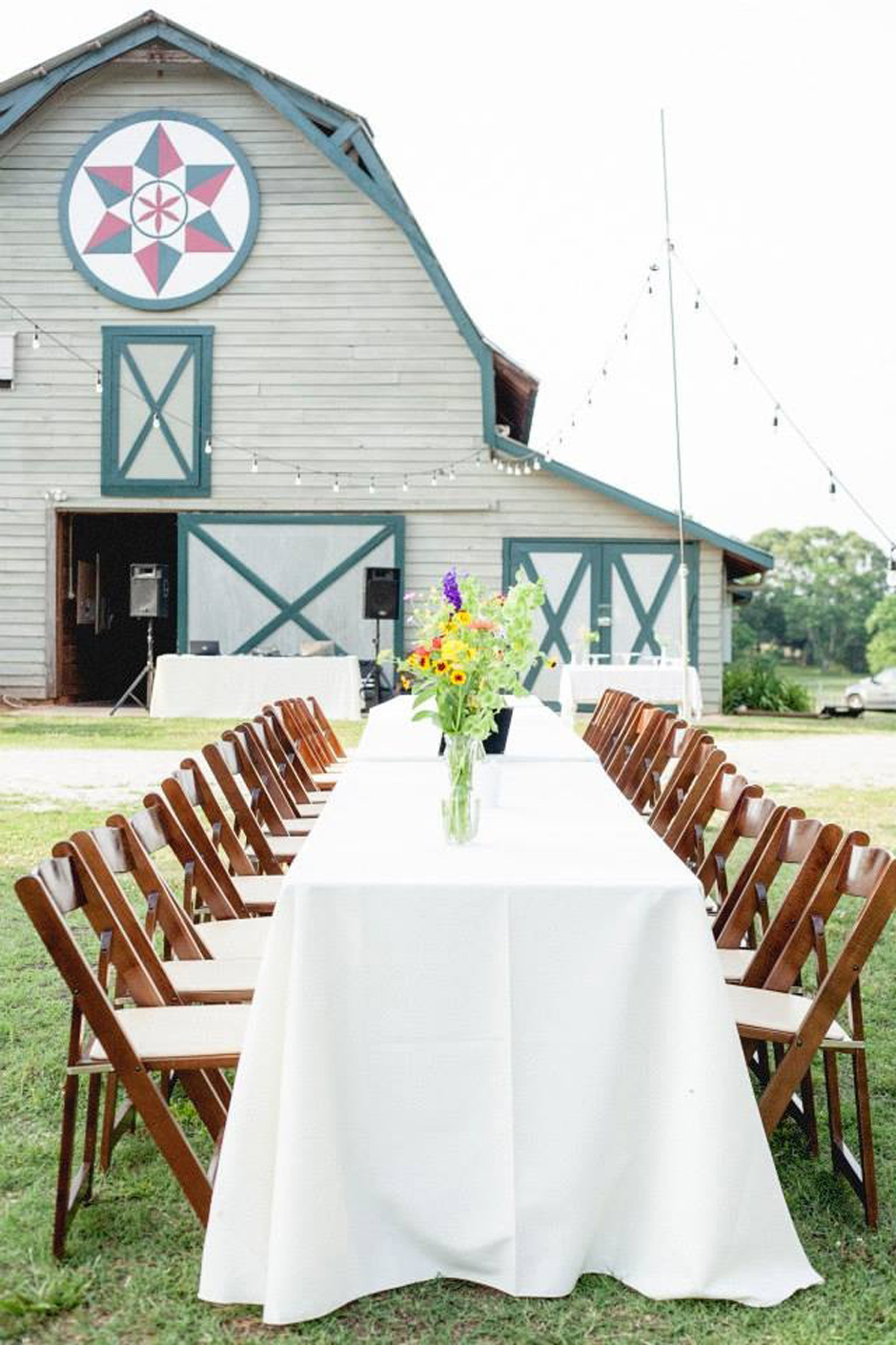 Al fresco dining at wedding reception in front of barn