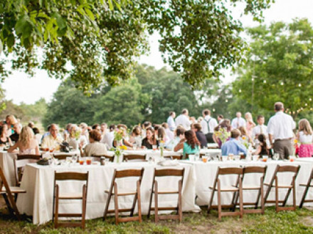 Al fresco wedding reception with family-style tables and wooden folding chairs.