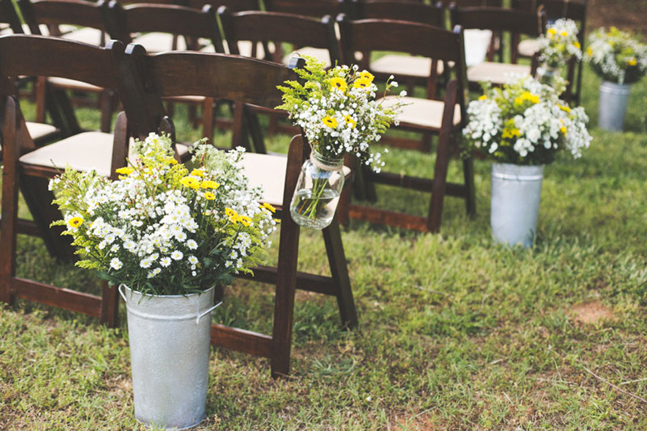 Wedding ceremony with aisle markers of yellow and white wildflowers in mason jars and galvanized buckets