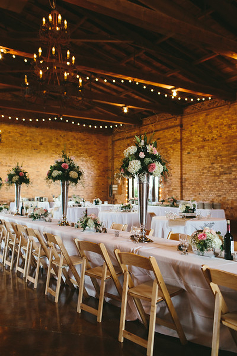 Wedding reception tables with tall, upright centerpieces and wooden folding chairs.