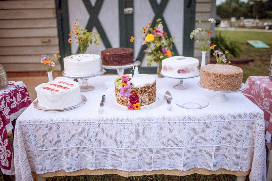Mixed cake station with burlap and lace tablecloth for a wedding.