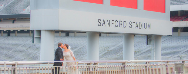 bride and groom kissing in front of sanford stadium