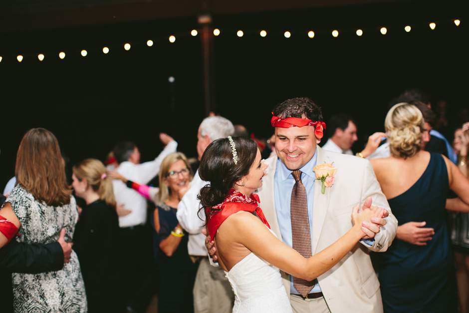 Bride and groom dancing with red bandanas.