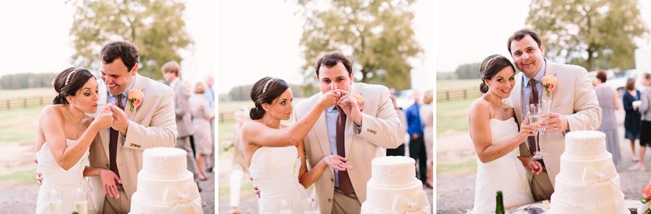 Bride and groom cutting a wedding cake at barn wedding
