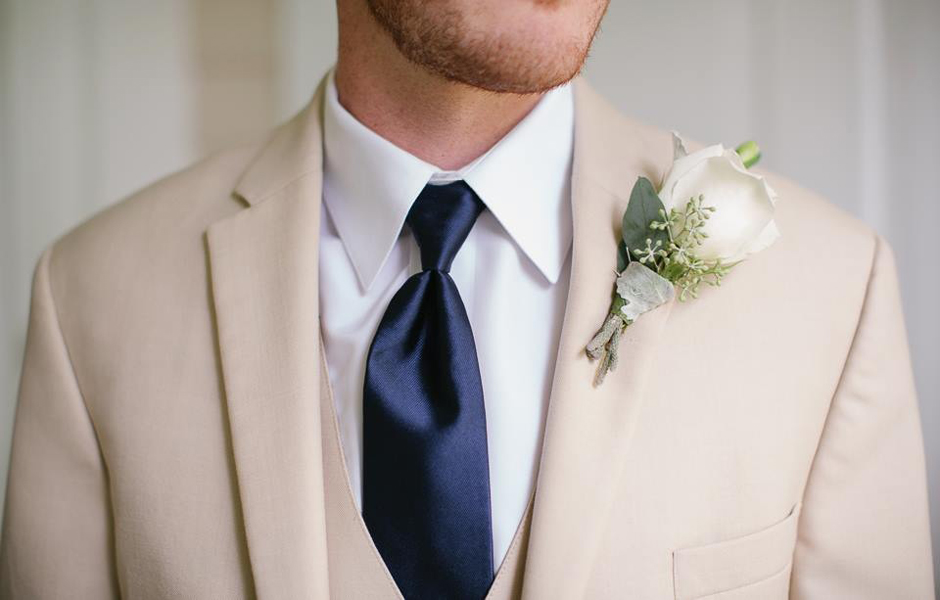 Groom wearing khaki-colored tux, navy tie, and cream-colored rose boutonniere.