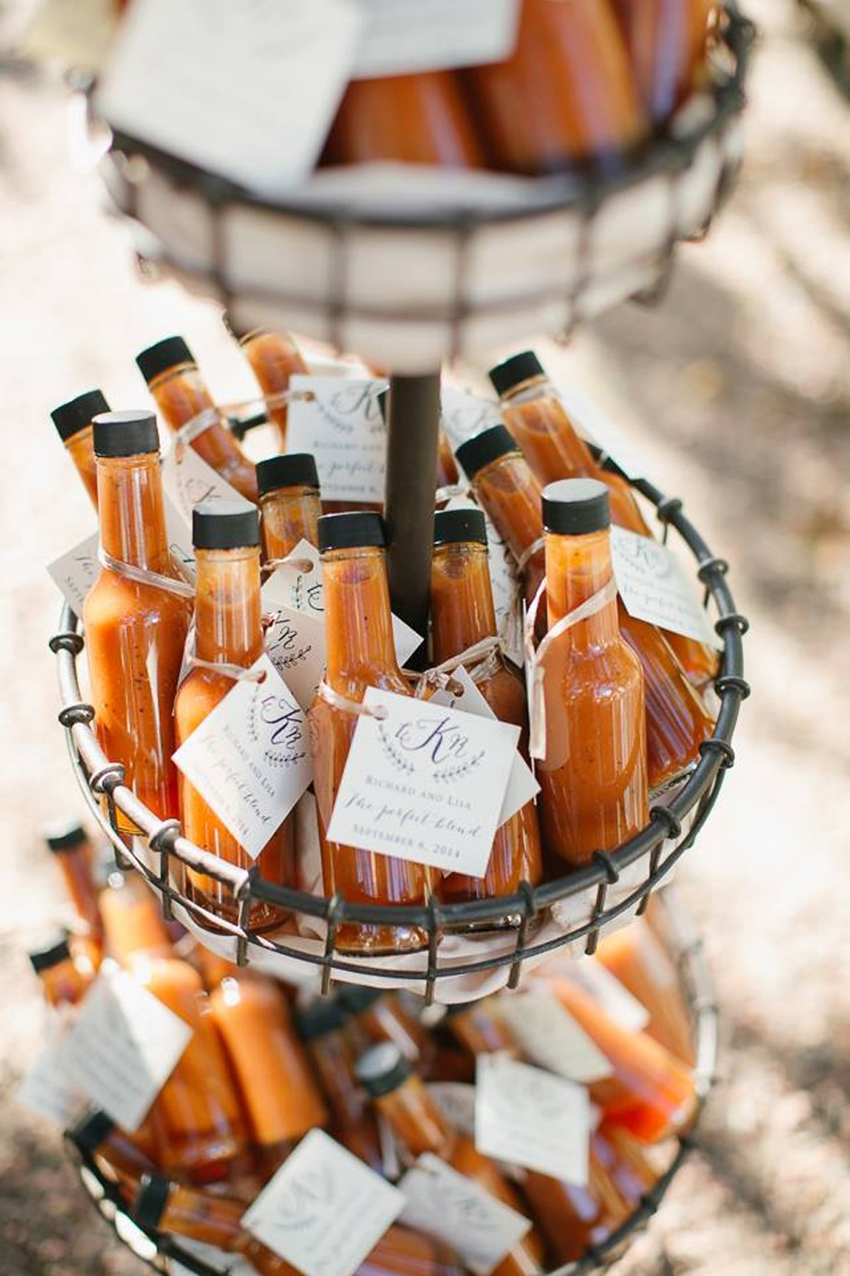 Miniature bottles of hot sauce gathered in a basket and used as wedding favors.