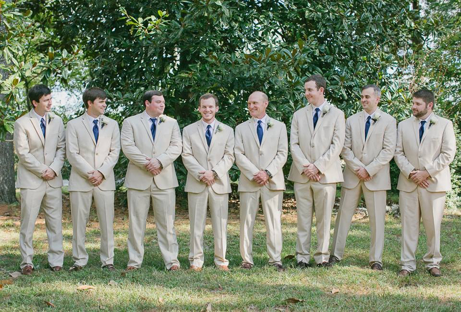 Groomsmen gathered together before wedding in tan, khaki-colored tuxes.