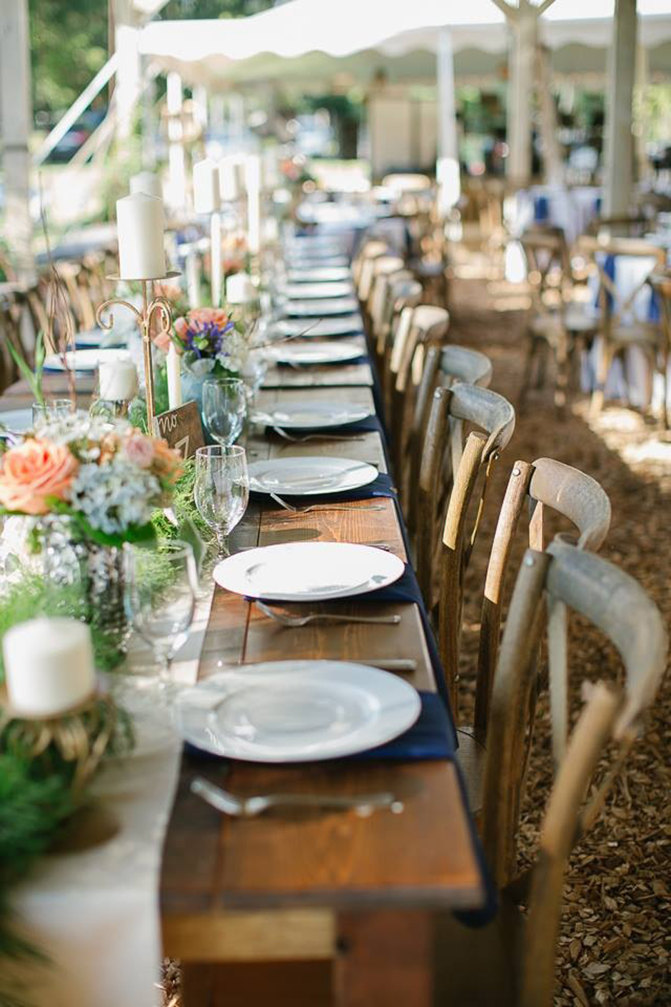 Peach, cream, and navy wedding reception with farm tables and crossback vineyard chairs.