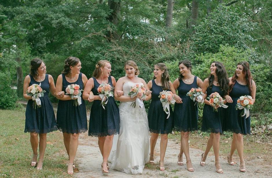 Bridesmaids gathered around bride on dirt road