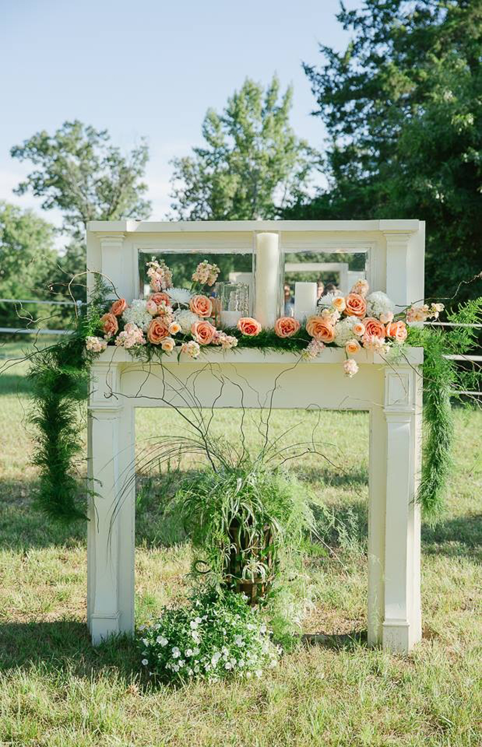 Rustic wedding ceremony backdrop -- antique mantle adorned with peach and cream roses.