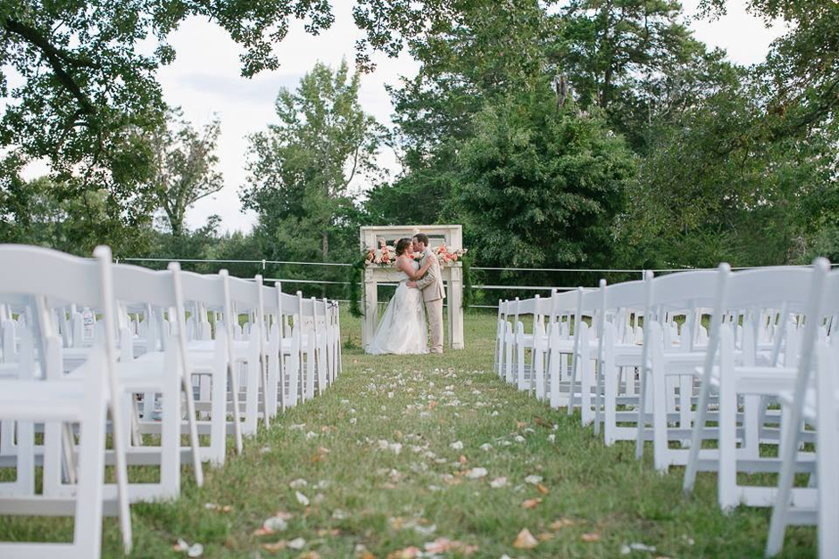 Bride and groom standing at ceremony location surrounded by white wedding chairs.