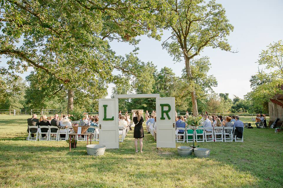 Large moss letters at rustic ceremony entrance.